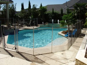 Architecture-Awesome-Cement-Deck-With-Glass-Fence-In-Marvelous-Swimming-Pool-Design-Beautiful-Above-Ground-Pool-Deck-Ideas-With-Cool-And-Beautiful-Design-Swimming-Pool-With-Fence-Surrounding-Decor