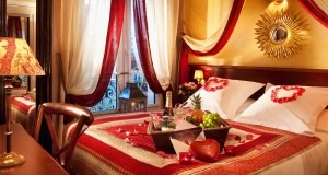 romantic-honeymoon-suite-bedroom-design-in-red-white-and-gold-color-with-beautiful-bed-set-with-red-heart-ornaments-and-decorative-bed-cover-plus-amazing-golden-sun-shaped-wall-decor-decorating-ideas